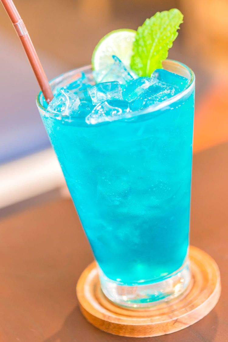 Blue Long Island Iced Tea drink with straw and mint garnish