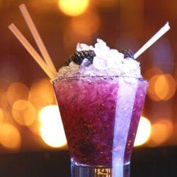 Blue Nectar Blackberry Bramble cocktail in front of blurred lights background