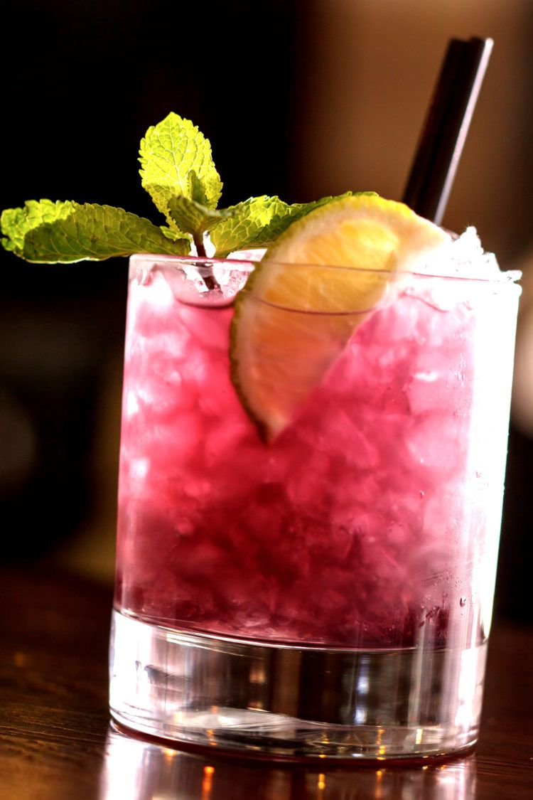 Blue Nectar Blackberry Bramble cocktail on bar with mint garnish