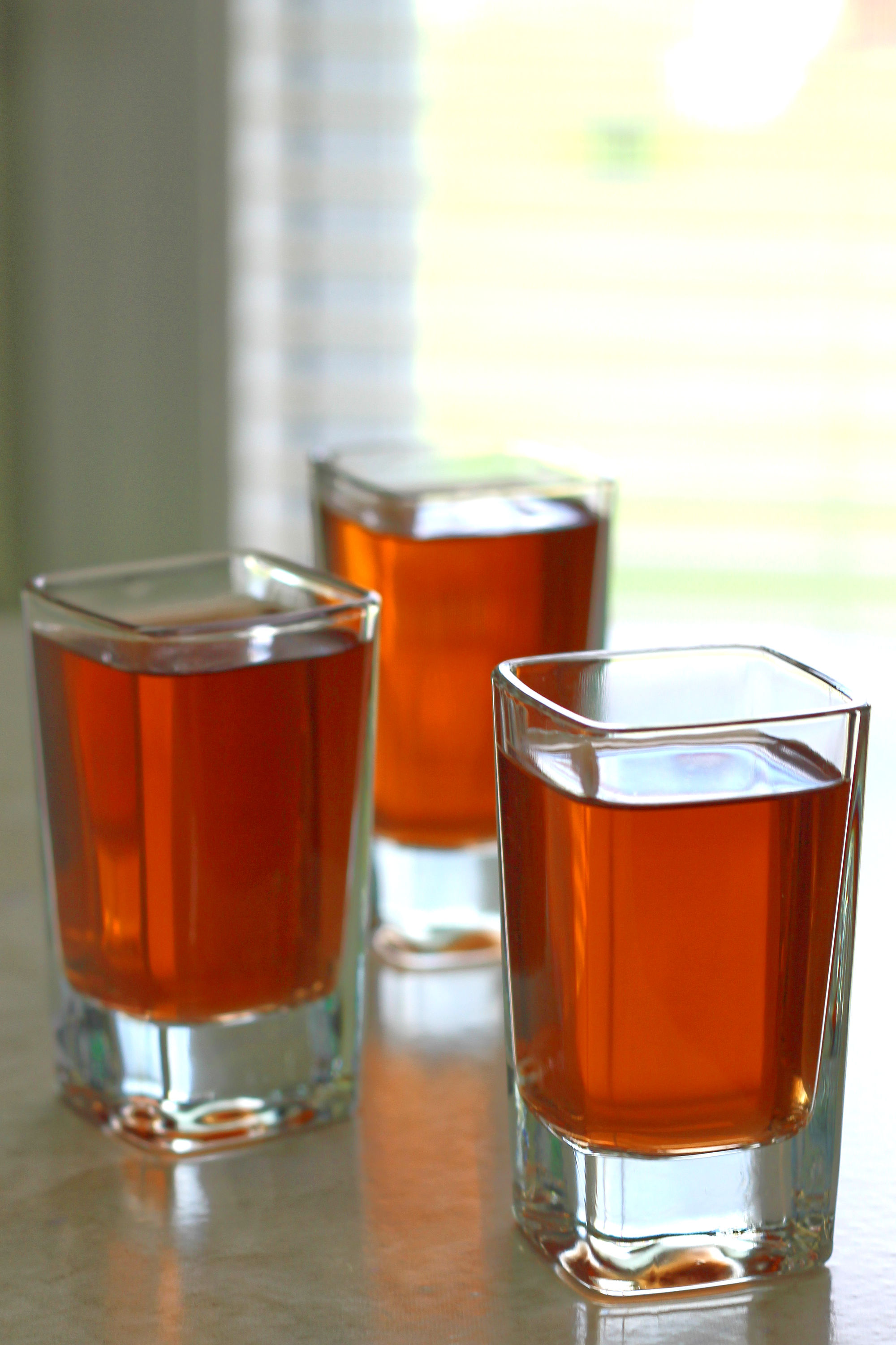 Three Kahlúa drinks in shot glasses on table