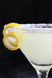 Closeup of yellow drink with lemon garnish