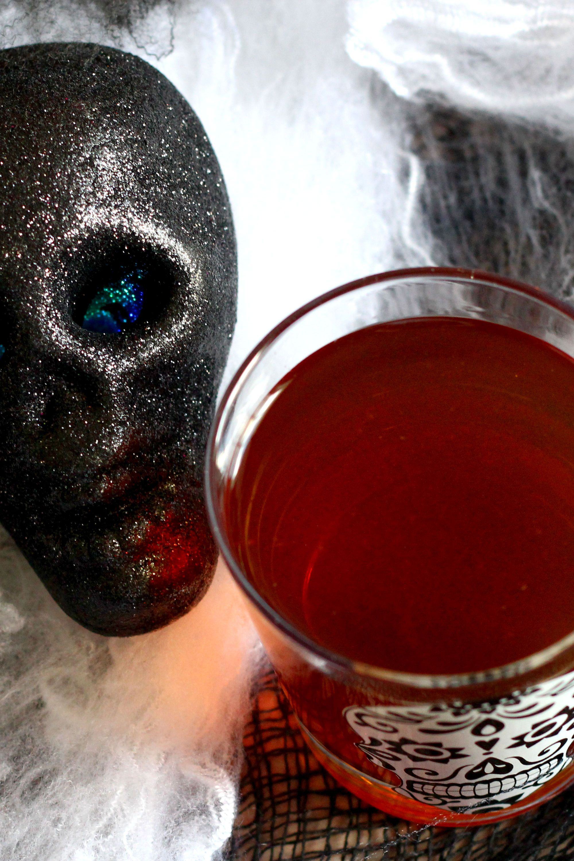 Cocktail surrounded by Halloween webbing and a black skull