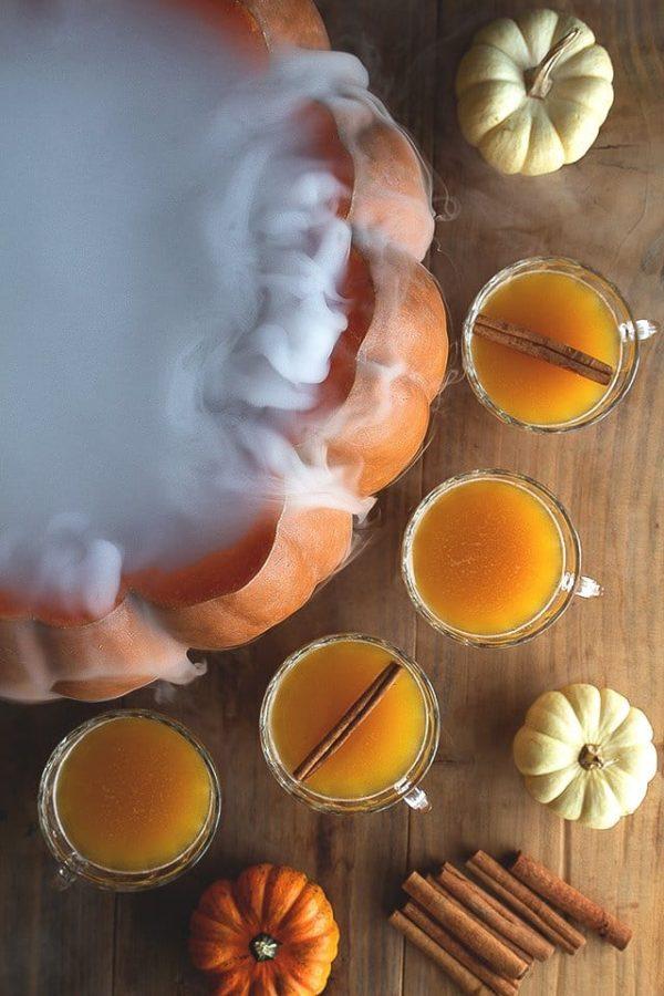 Orange cocktails around a pumpkin with dry ice fog