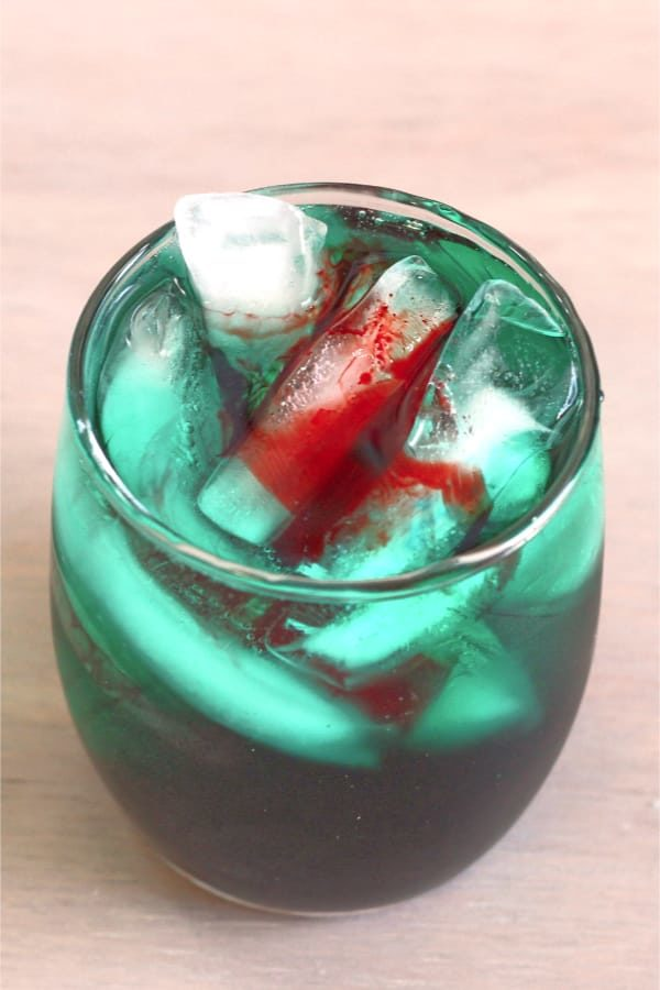 Greenish cocktail with appearance of blood floating on top
