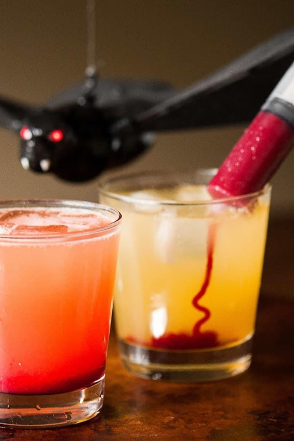 Yellow cocktail with red syrup being injected into it