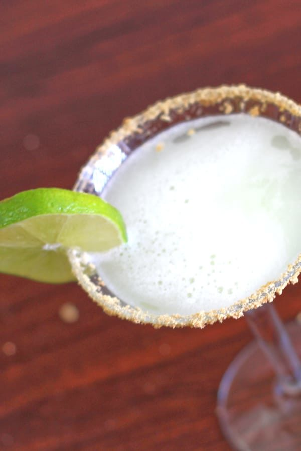 Key Lime Martini in glass with lime wheel and graham cracker crumb rim