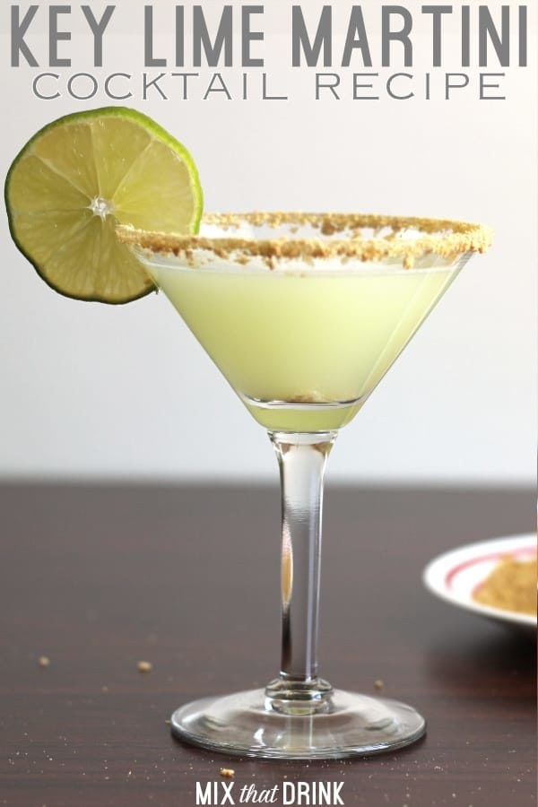 Pale green Key Lime Martini in glass with lime wheel and graham cracker crumb rim