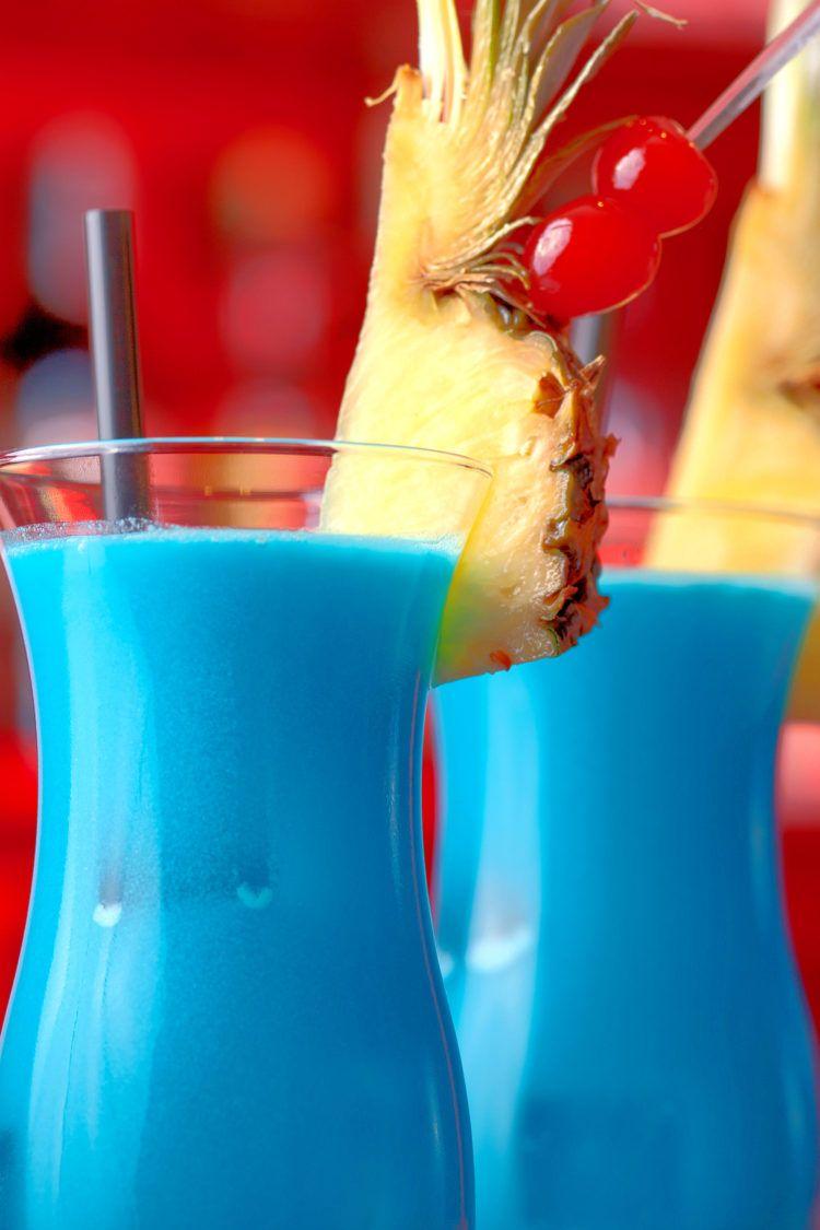 Two Blue Hawaiian drinks on bar with pineapple and cherry garnish
