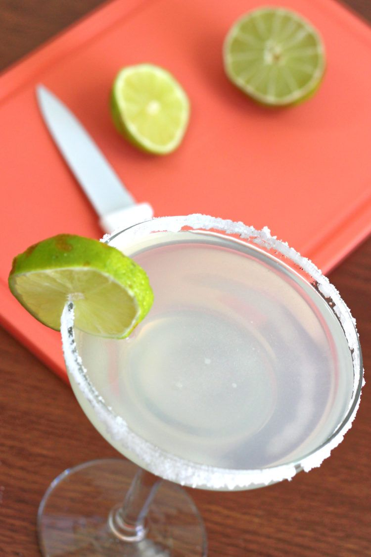 Overhead shot of margarita drink in glass beside cutting board with limes